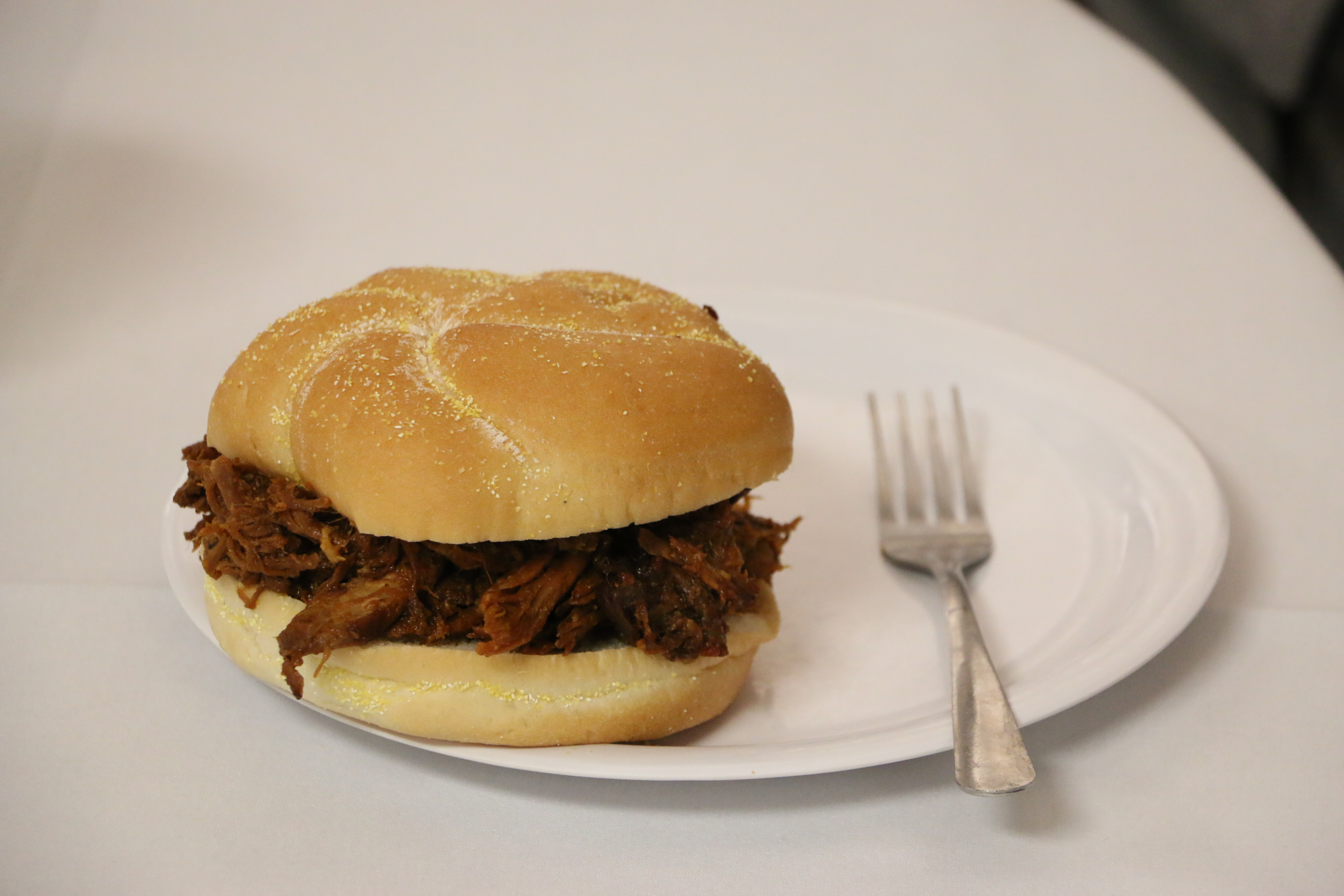 Roast beef in a fresh bun on a white plate with a fork.