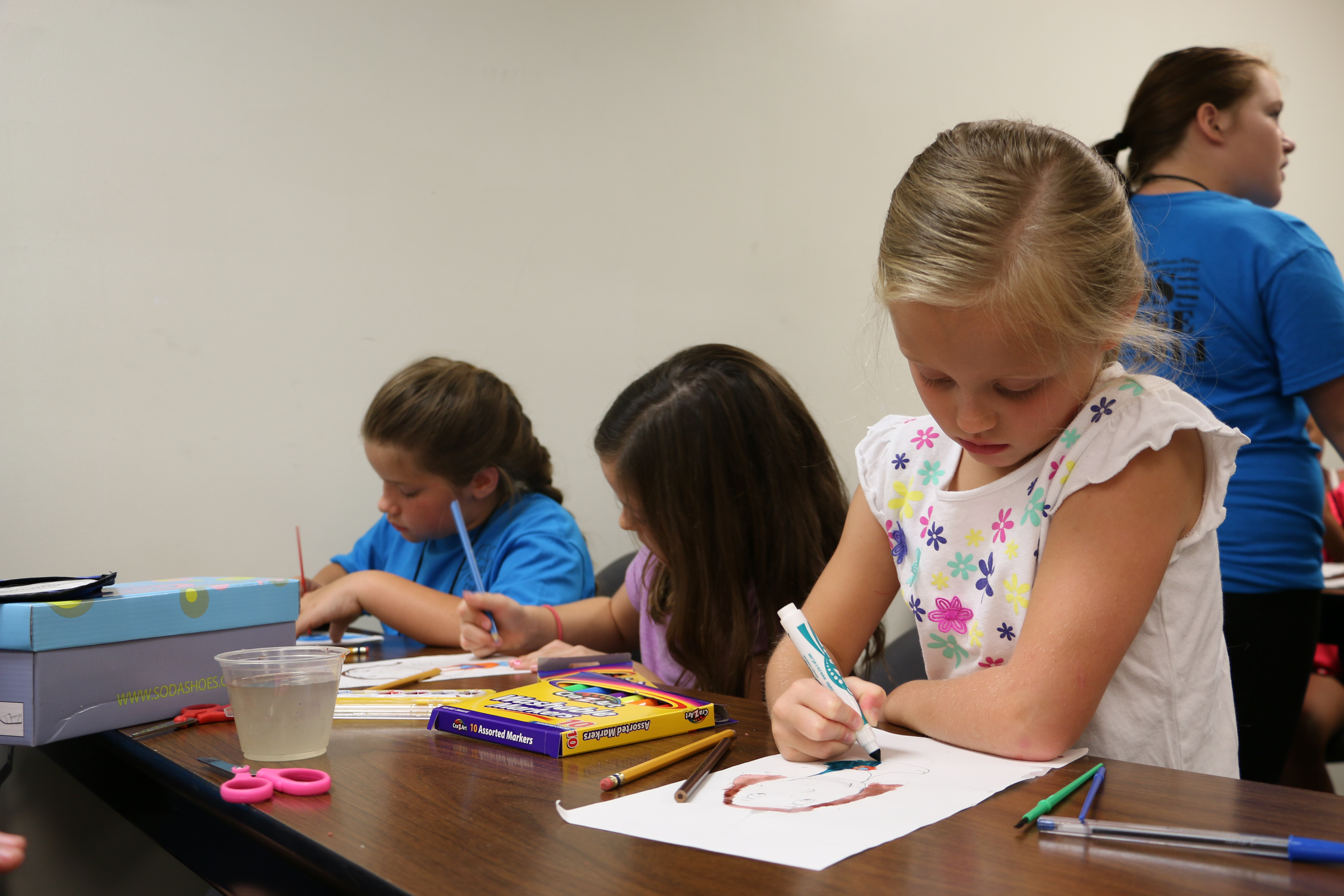 Three young girls sitting at a table and painting with brushes, pencils, and markers.