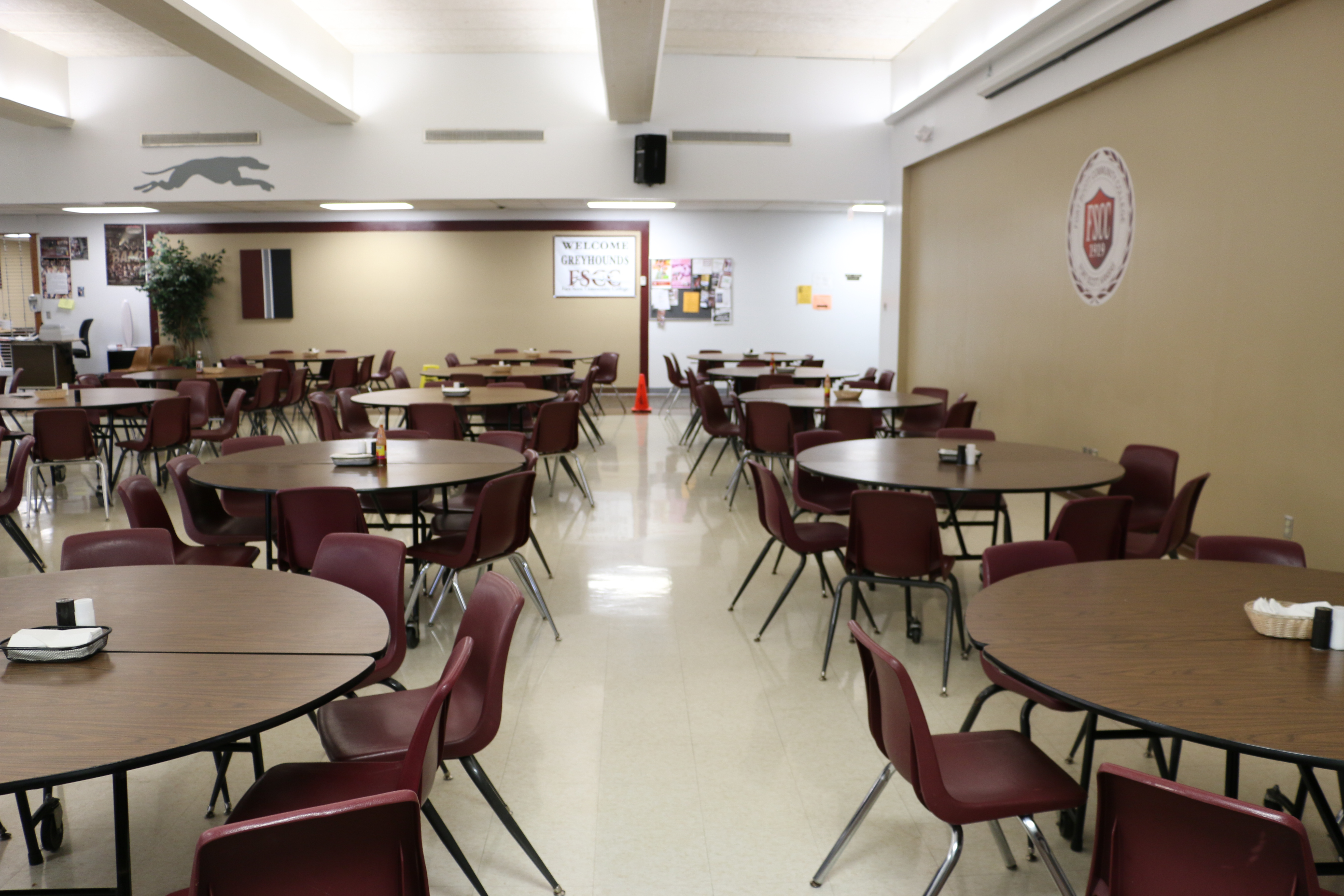 FSCC's cafeteria, with its round tables and maroon plastic chairs all lined up in columns and rows.