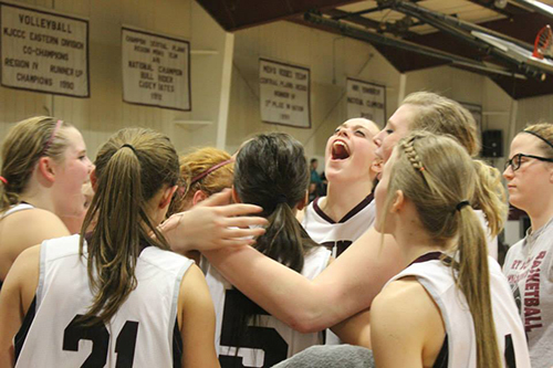 The women's basketball team huddled together during a game.