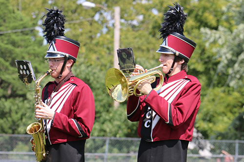 A saxophone player and a French horn player in their band uniforms, performing on the field.