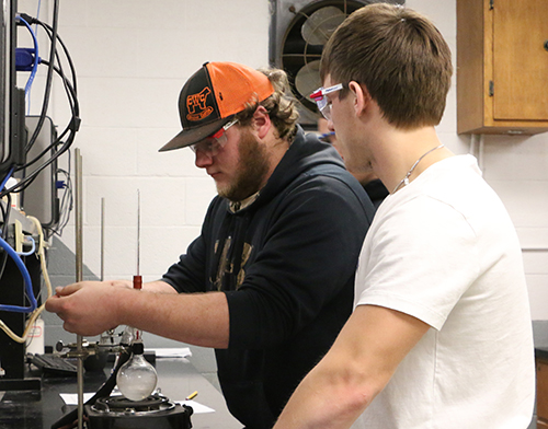 Two male students working together at a chemistry station.