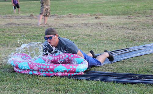 A student from the Collegiate Farm Bureau Club sliding down a slip-n-slide and about to land in a kiddie pool full of water.
