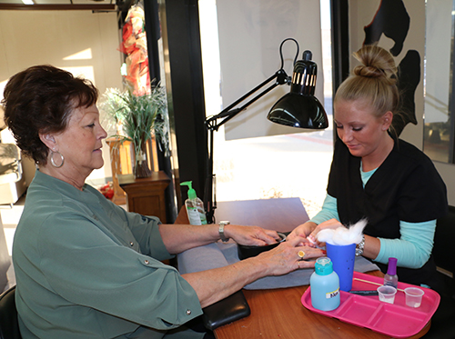 A manicurist giving a customer a manicure.