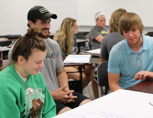 Several students, who have been broken up into groups of three, working on projects together in English class.