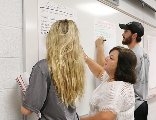 Two students and their teacher writing questions on the whiteboard.