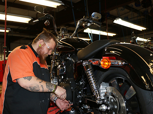 A student working on a Harley-Davidson bike.