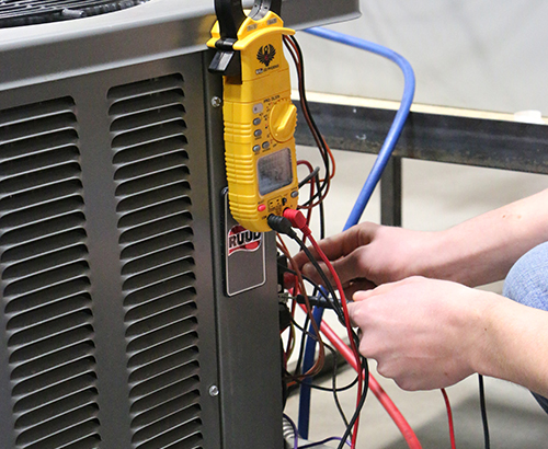 An HVAC student using a diagnostics device on a air conditioner to check its readings.