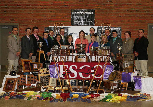All the students of the Livestock Judging team and their instructors standing behind a large display of all the awards the team has won.