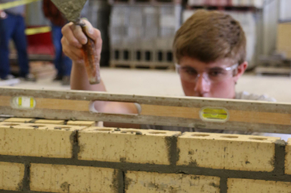 A masonry student using a level to confirm the wall he build is straight.