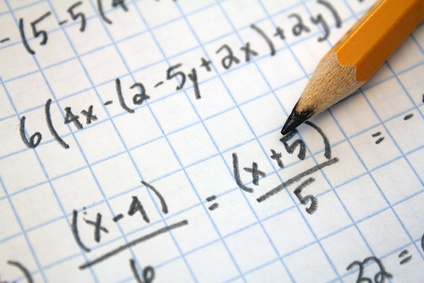 A pencil laying on a sheet of graphing paper covered in math problems.