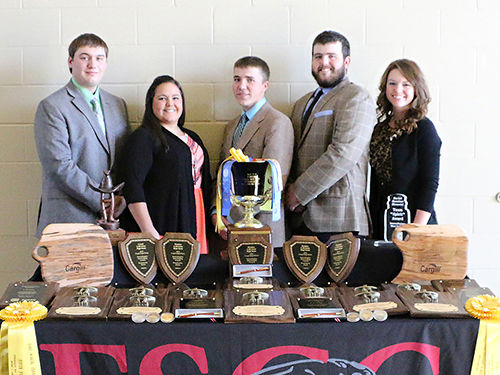 Four members of the Meat Judging Team and their coach standing behind a display of all the trophy they've won.