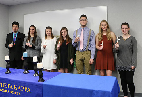 Several students from Phi Theta Kappa posing together while holding candles.