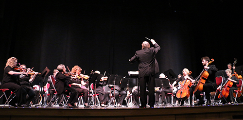 FSCC's orchestra performing on stage with the conductor in mid-swing of his baton.