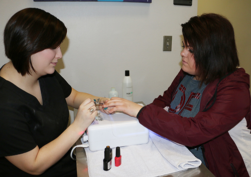 A student getting a manicure.