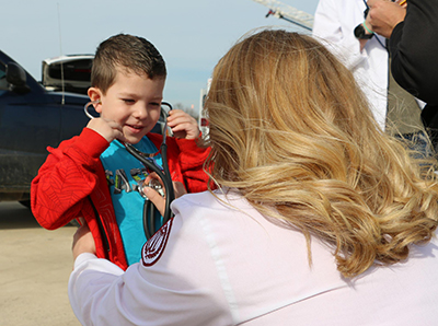 A nursing student showing a young boy how to use a stethoscope.