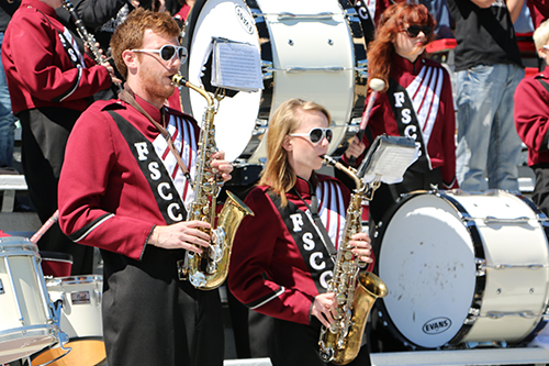 Band members, dressed in their uniforms, playing saxophones and drums at a football game.