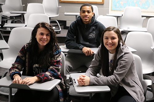 Three students smiling into the camera while sitting at their desks.