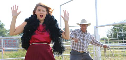 A young lady in a dress and feather boa being lassoed by a cowboy.
