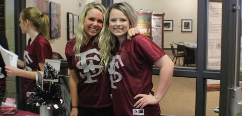 Two female students smiling excitedly at their recruitment desk.