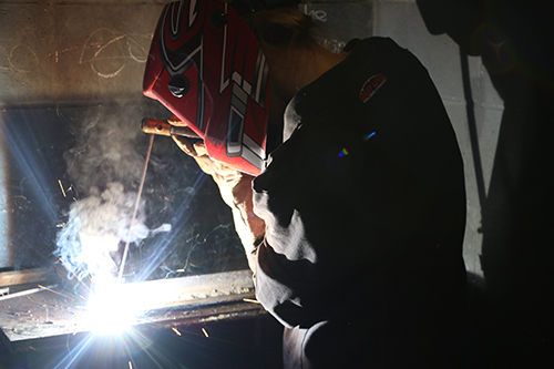 A welding student using her welding tool while wearing a stylized protective mask.