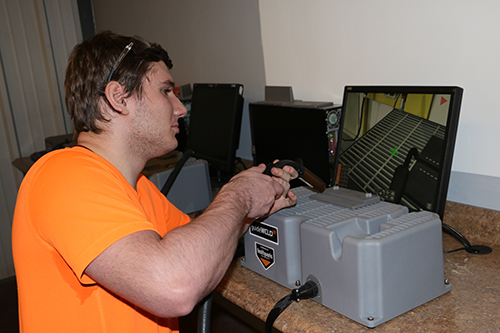A welding student practicing spot welding in a computer simulator.